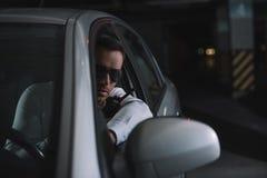allvarligt manligt hemligt medel i solglasögon som gör bevakning och använder talkiewalkie royaltyfri bild