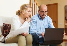 Allvarligt mogna par med dokument och bärbara datorn Arkivbild