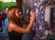Ally Breelsen faz uma anotação na casa do Juliet fotografia de stock royalty free