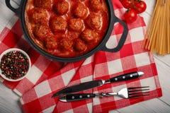 Almôndegas no molho de tomate com especiarias em uma frigideira em uma placa de madeira branca imagem de stock royalty free