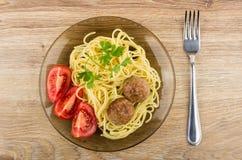 Almôndegas fritadas com massa e tomates na placa e na forquilha Imagem de Stock