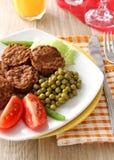 Almôndegas saborosos, ervilhas verdes e tomates na placa Fotografia de Stock