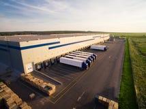 Almacén de distribución con los camiones de diversa capacidad foto de archivo libre de regalías
