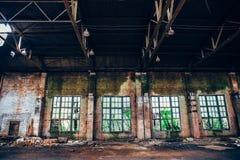 Almacén espeluznante industrial abandonado dentro con las ventanas grandes, edificio oscuro viejo de la fábrica del grunge imagen de archivo libre de regalías