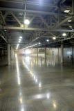 Almacén vacío grande dentro en el edificio industrial con un alto techo y una iluminación artificial foto de archivo libre de regalías