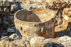 Almacenamiento antiguo antiguo del pote con el ornamento entre las piedras de las ruinas imagenes de archivo
