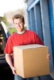 Almacenamiento: Hombre que lleva la caja el almacenamiento Imagen de archivo