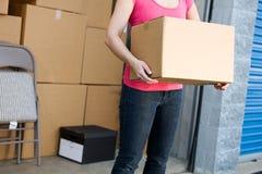 Almacenamiento: Mujer con la unidad de almacenamiento completa detrás Fotos de archivo libres de regalías