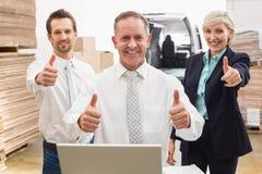 Almacene al equipo que sonríe en la cámara que muestra los pulgares para arriba Imagen de archivo libre de regalías