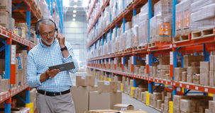 Almacene al trabajador que usa la tableta digital mientras que comprueba los paquetes almacen de metraje de vídeo