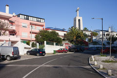 Almada in Portugal. Street, apartment buildings and Cristo Rei monument in the background in Almada, Portugal Royalty Free Stock Photo
