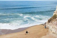 Almagreirastrand met surfer en visser die op Atlantische kansen in Ferrel, Peniche, centrale westelijke Kust wachten van Portugal Stock Afbeeldingen