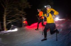 ALMATY, CAZAQUISTÃO - 18 DE FEVEREIRO DE 2017: Competições da noite nos montes da cidade de Almaty, no Trailrunning Imagem de Stock