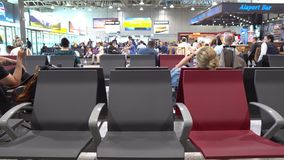 Almaty International Airport. Three empty seats at near the departure gate while at background a woman is using her smartphone stock video footage