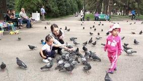 Almaty, Kazajistán - 20170531 - madre enseña hija a cómo alimentar palomas en parque almacen de video