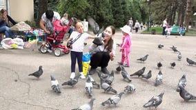 Almaty, Kazajistán - 20170531 - paloma vuela en muchachas da en parque metrajes