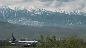 Boeing 737 of SCAT airlines. Scenery landscape with mountains stock video footage