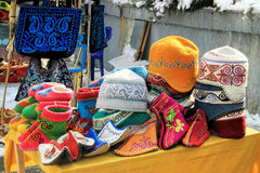 Almaty, Kazakhstan: traditional souvenirs. Various of Kazakh traditional souvenirs ethnic hats, shoes and horsewhip  with ornaments in market in Kok-tobe park Stock Photo