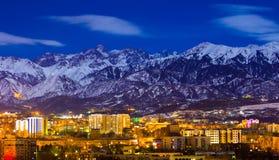 Almaty och berg under månskenet royaltyfri foto