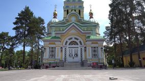 Almaty Orthodox Church. Almaty Russian Orthodox Christian Zenkov Ascension Cathedral of the lord back entrance view in Panfilov park on a sunny blue sky day stock video