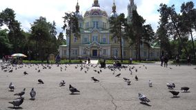 Almaty Orthodox Church. Almaty Russian Orthodox Christian Zenkov ascension cathedral low angle frontal view in Panfilov park with pigeons and people on a sunny stock video footage