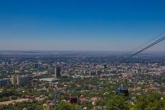 Almaty stadssikt från den Koktobe kullen och kabinen av kabelbilen, Kazak Fotografering för Bildbyråer