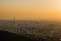 Almaty-Stadt im Nebel im Sonnenuntergang mit Smog und im Staub in der Luft, lizenzfreies stockbild