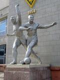 Almaty - vecchia scultura dei giocatori di football americano Fotografie Stock Libere da Diritti