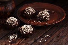 Almendras garapiñadas del chocolate del primer con el coco en una tabla de madera rústica oscura Dulces hechos en casa Foco selec fotos de archivo