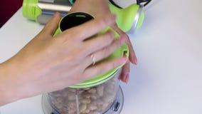 Almendras peladas en un cuenco de la licuadora para moler Una mujer cubre el cuenco con una tapa y ata una licuadora Cocinar el r almacen de metraje de vídeo