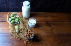 Almendras y leche fresca en la madera fotos de archivo