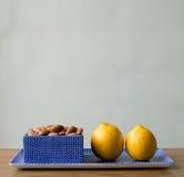 Almendras y limones en plato azul Foto de archivo libre de regalías
