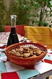Almendras y nueces en cesta en la tabla del mosaico Fotografía de archivo libre de regalías