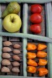 Almendras y pimientas anaranjadas en una tabla Fotos de archivo libres de regalías