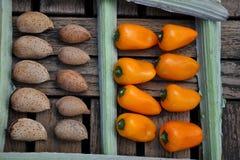 Almendras y pimientas anaranjadas en una tabla Foto de archivo