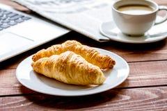 Almoço de negócio com croissant e portátil na mesa de madeira fotografia de stock royalty free