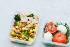 Almoço delicioso e saudável Carne da galinha com vegetais fervidos, os tomates maduros e os ovos no recipiente no fundo cinzento  imagens de stock royalty free
