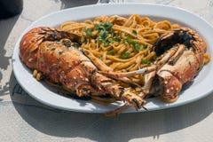 Almoço delicioso pelo mar Uma placa branca dos espaguetes com as lagostas enormes na grade foto de stock