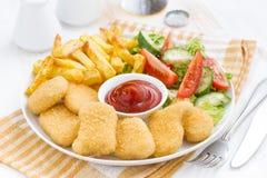 Almoço do fast food com pepitas, batatas fritas e vegetal de galinha Fotografia de Stock Royalty Free