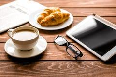 Almoço do homem de negócios em casa com café, croisant e dispositivo Imagem de Stock