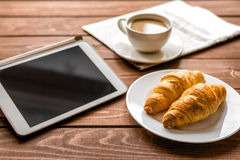 Almoço do homem de negócios em casa com café, croisant e dispositivo Fotos de Stock Royalty Free