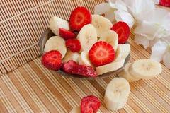Almoço do verão: corte bananas e morangos fotos de stock royalty free