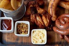 Almoço entusiasta alemão no bar Salsichas grelhadas, couve cozido, pão torrado, molho Petisco da cerveja fotografia de stock royalty free