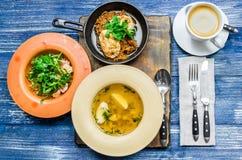 Almoço: frigideira com carne e ervas, sopa amarela, salada dos vegetais e ervas, café e cutelaria, em um fundo azul da sarja de N Imagens de Stock Royalty Free