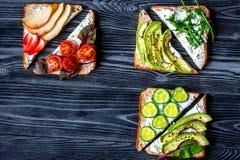 Almoce com os sanduíches do triângulo na opinião superior do fundo escuro da tabela Fotografia de Stock