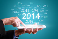 Almofada da tabuleta tocante do homem de negócios pelo ano novo 2014 Imagem de Stock