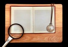 Almofada de escrita e lupa e relógio fotos de stock royalty free