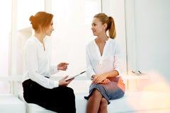 Almofada de toque da posse do empresário da jovem mulher ao dizer algo a seu sócio durante a reunião de negócios, Fotos de Stock Royalty Free