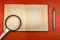 Almofada e lupa velhas de escrita fotografia de stock