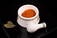 Almofariz cerâmico branco com pimenta vermelha raspada Foto de Stock